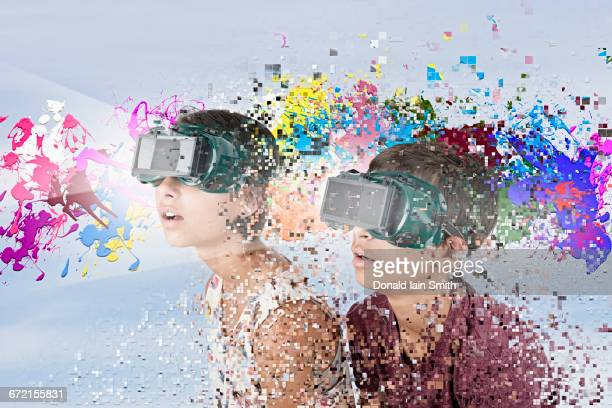 Mixed Race brother and sister watching paint splatter with VR goggles