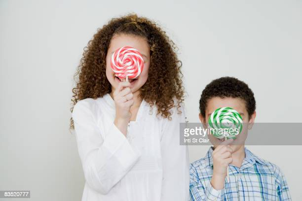 Mixed race brother and sister with oversized lollipops