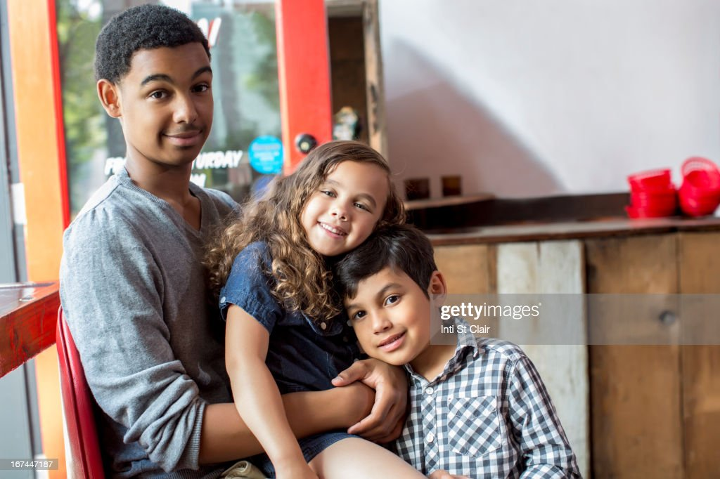 Mixed race brothers and sister smiling together : Stock Photo
