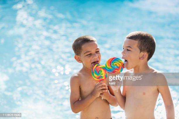 Mixed race brothers by pool licking lollipops
