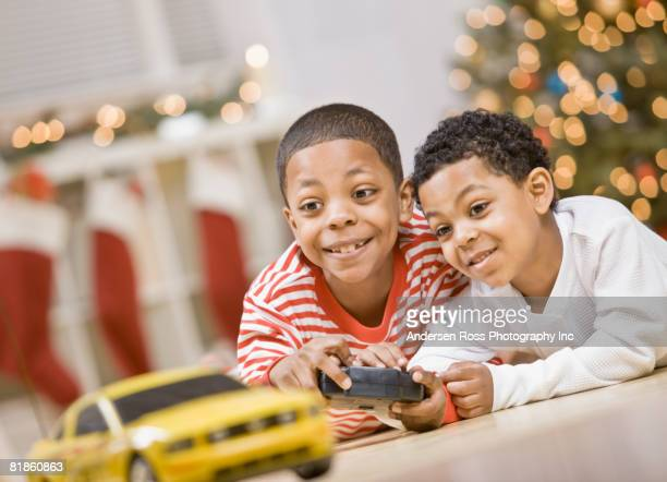 mixed race brothers playing with remote control car - remote control car games stock pictures, royalty-free photos & images