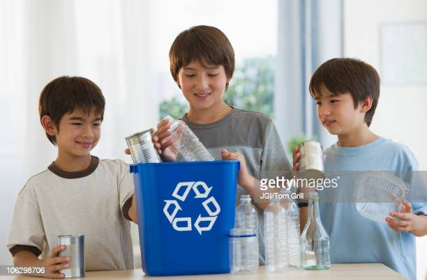 Mixed race brothers recycling plastic bottles and tin cans