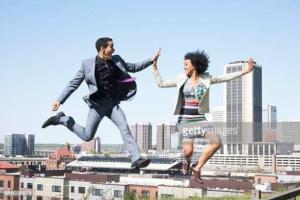 Mixed Race business people jumping and high-fiving in city