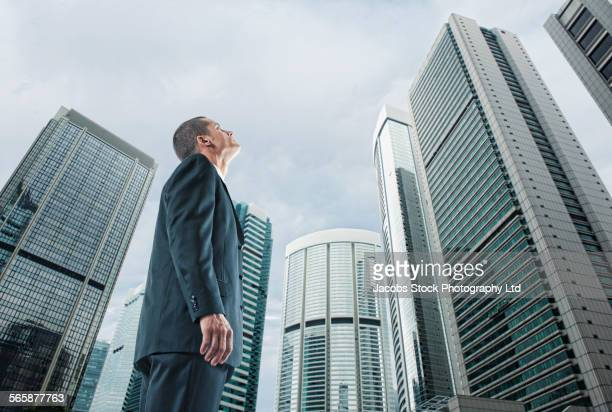 Mixed race businessman admiring highrise buildings in cityscape