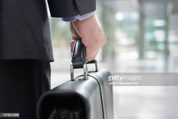 Mixed race businessman carrying briefcase