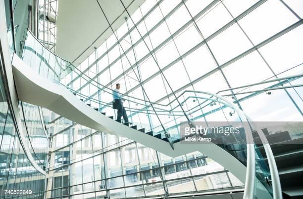 mixed race businessman descending staircase - movimiento hacia abajo fotografías e imágenes de stock