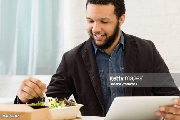 Mixed race businessman eating salad