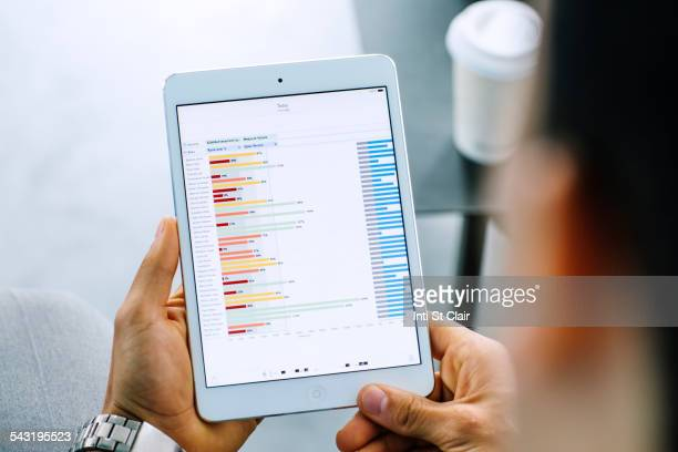 mixed race businessman examining graph on digital tablet - over the shoulder view stock pictures, royalty-free photos & images