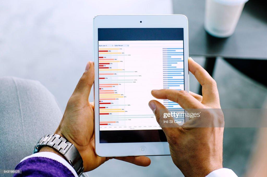 Mixed race businessman examining graph on digital tablet : Stock Photo