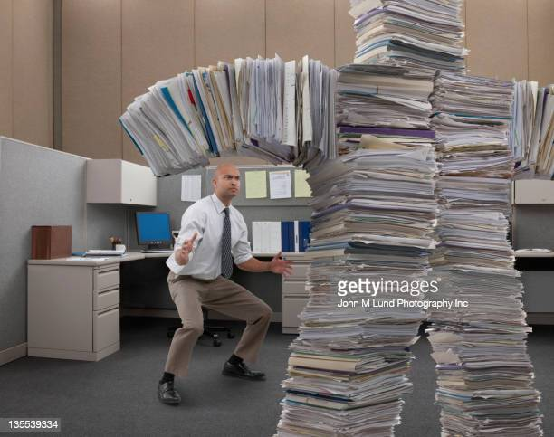 mixed race businessman facing paperwork monster - big bobs stock photos and pictures