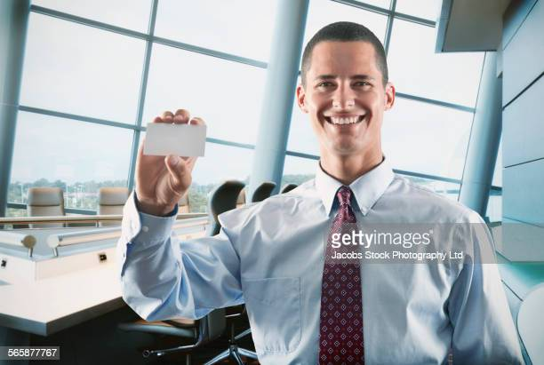 Mixed race businessman holding business card in conference room