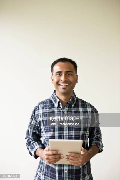 mixed race businessman holding digital tablet - indian subcontinent ethnicity stock pictures, royalty-free photos & images