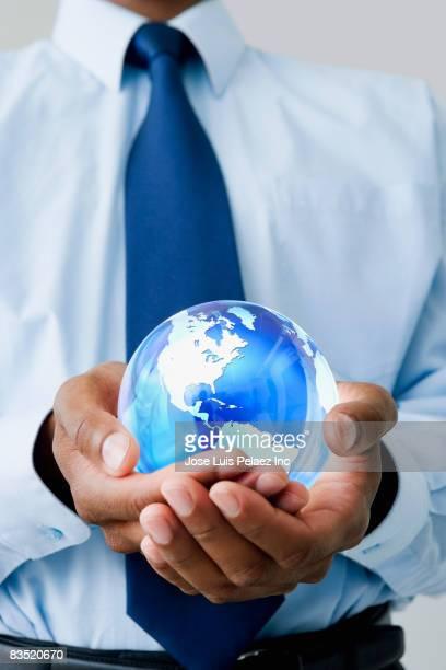 Mixed race businessman holding glass globe