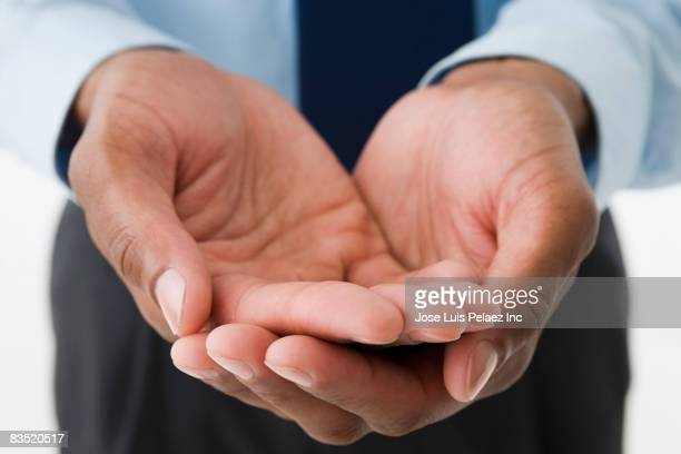 mixed race businessman holding out empty hands - hands cupped stock pictures, royalty-free photos & images