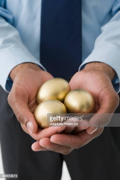 Mixed race businessman holding three golden eggs