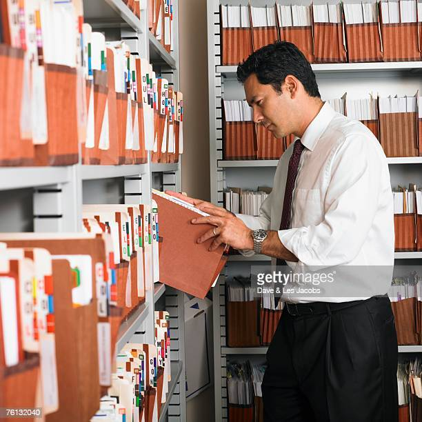 Mixed Race businessman in file room