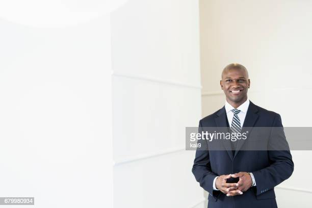 Mixed race businessman in suit smiling at camera