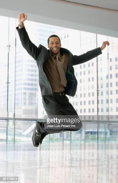 mixed race businessman jumping in office - geschäftskleidung stock-fotos und bilder
