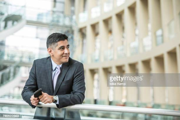 mixed race businessman leaning on railing in lobby holding cell phone - abbigliamento da lavoro formale foto e immagini stock