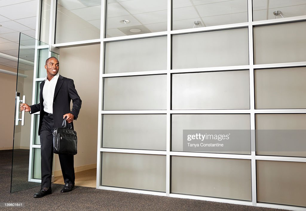 Mixed race businessman leaving modern office : Stock Photo