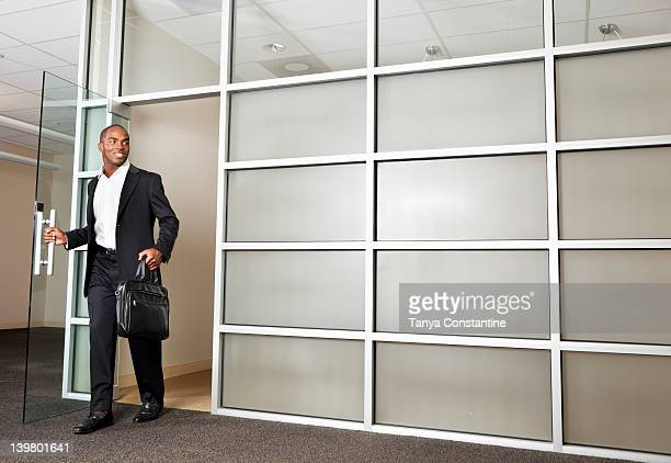 mixed race businessman leaving modern office - door man stock photos and pictures
