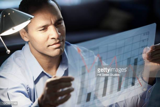 mixed race businessman looking at bar graph - economist stock pictures, royalty-free photos & images