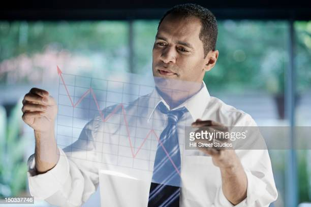mixed race businessman looking at line graph - economist stock pictures, royalty-free photos & images