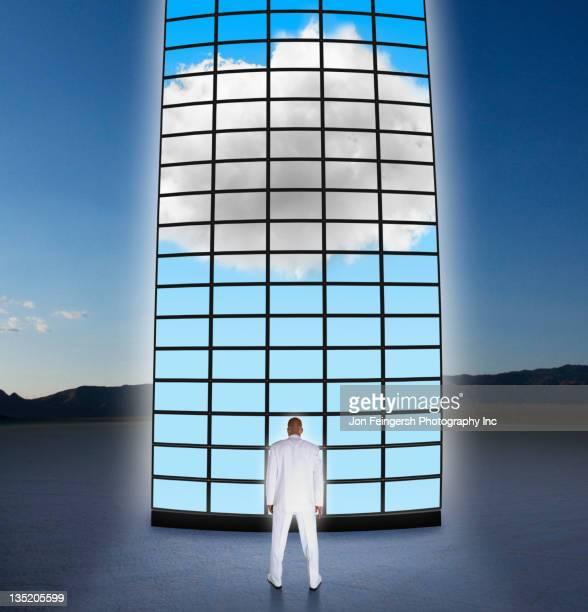 Mixed race businessman looking at towering monitors