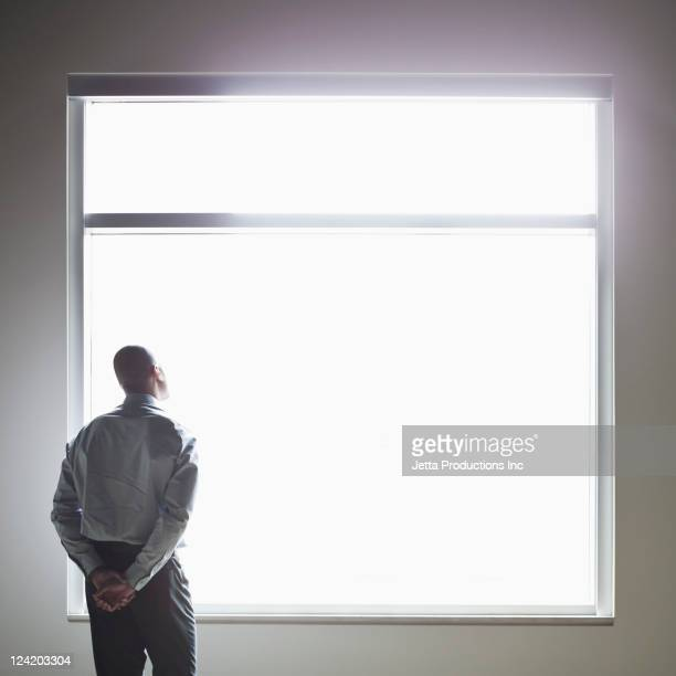 Mixed race businessman looking out window