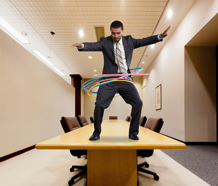 Mixed race businessman on conference table spinning plastic hoops - gettyimageskorea