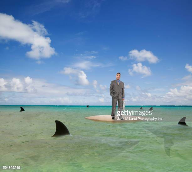 Mixed race businessman on island in sea of sharks
