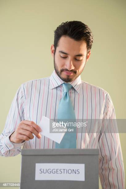 Mixed race businessman placing idea in suggestion box