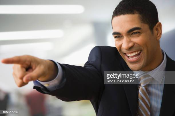 Mixed race businessman pointing