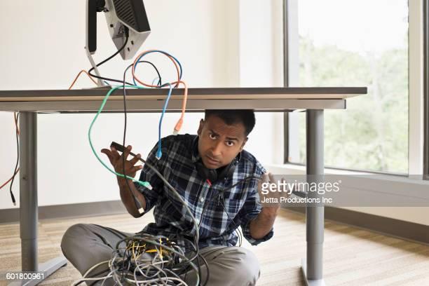 mixed race businessman repairing computer - bemühung stock-fotos und bilder