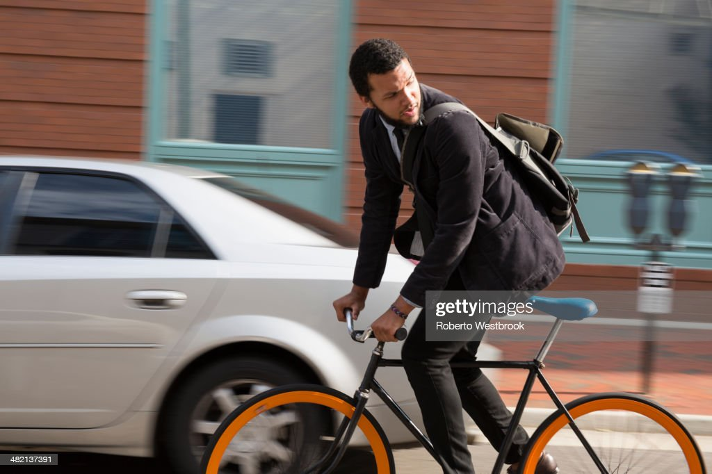 Mixed race businessman riding bicycle on city street : Stock Photo