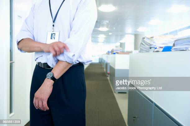 Mixed race businessman rolling sleeves in office