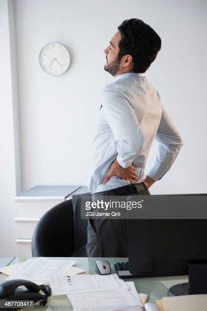 Mixed race businessman rubbing his back in office