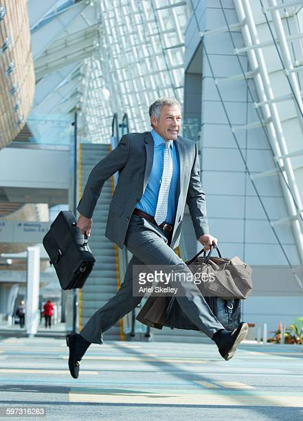 Mixed race businessman running in airport