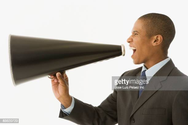 Mixed race businessman shouting into megaphone