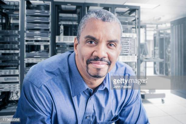 Mixed race businessman sitting in server room