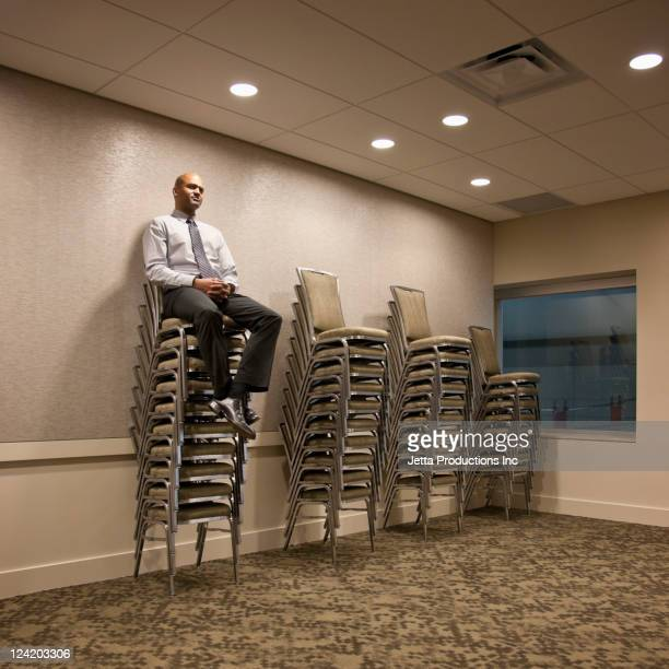 mixed race businessman sitting on stack of chairs - chairperson stock pictures, royalty-free photos & images