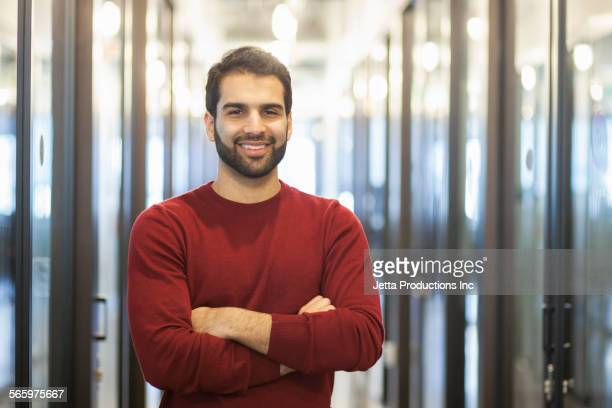 Mixed race businessman smiling in office hallway