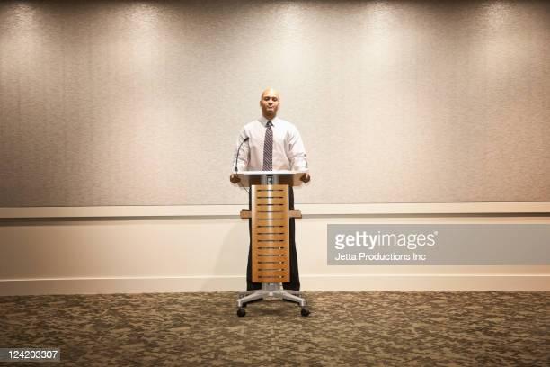 Mixed race businessman standing at podium