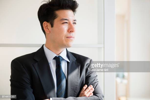 Mixed race businessman standing at window