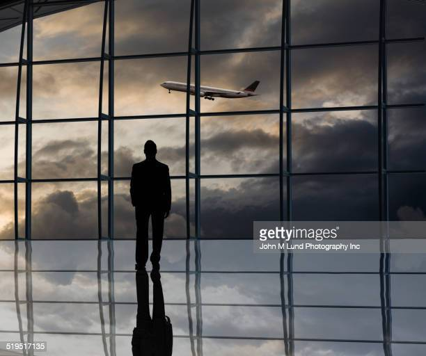 Mixed race businessman standing near window at airport