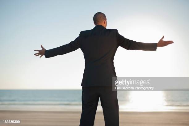 Mixed race businessman standing on beach with arms outstretched