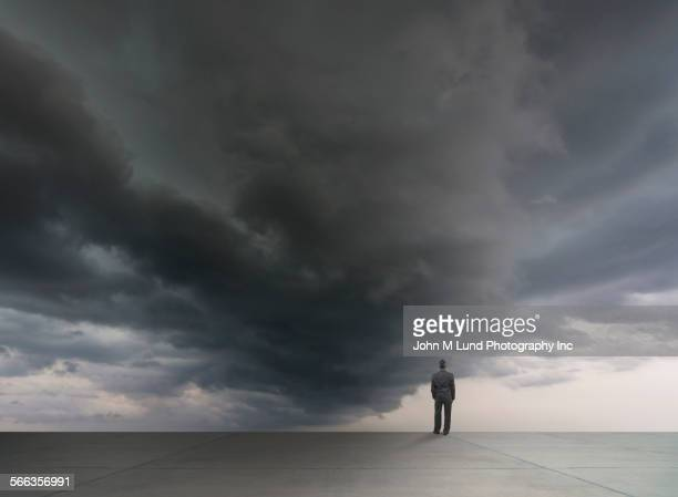 Mixed race businessman standing under stormy sky
