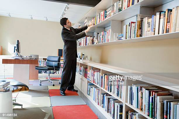 Mixed race businessman taking book from shelf