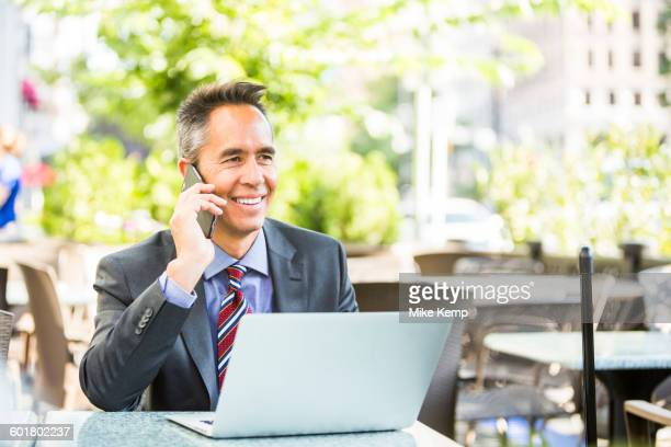 Mixed race businessman talking on cell phone in cafe