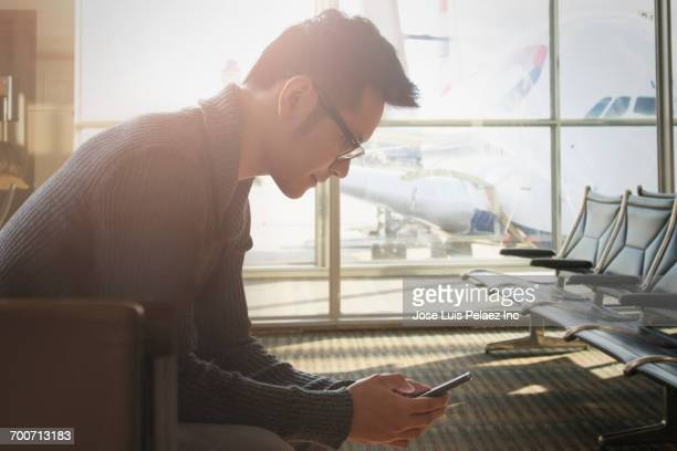 Mixed Race businessman texting on cell phone in airport